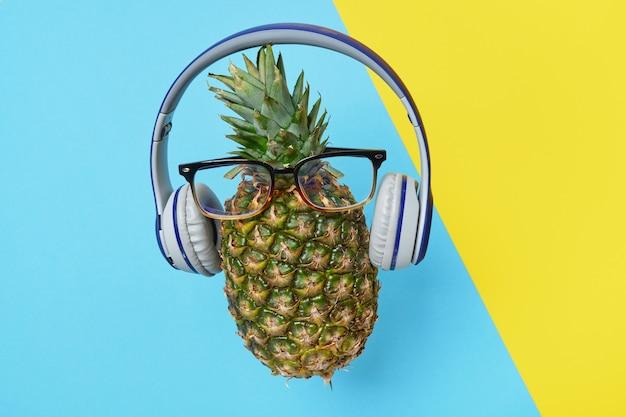 Een verse rijpe ananas in een bril met een draadloze koptelefoon op een blauwe en gele achtergrond