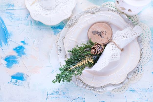 Een versierde witte tafel voor het nieuwe jaar en kerstmis, een vuren tak, een servet en een brok.