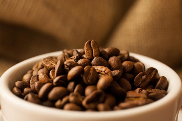 Een verstrooiing van koffiebonen met een kopje koffie.