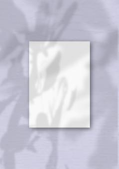 Een verticaal a4-vel wit gestructureerd papier op de zachte paarse muurachtergrond. mockup-overlay met de plantschaduwen. natuurlijk licht werpt schaduwen van de boom van geluk.