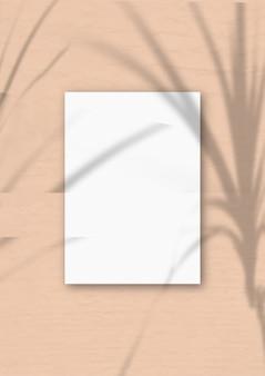 Een verticaal a4-vel wit gestructureerd papier op de zachtroze muurachtergrond. mockup-overlay met de plantschaduwen. natuurlijk licht werpt schaduwen van een tropische plant