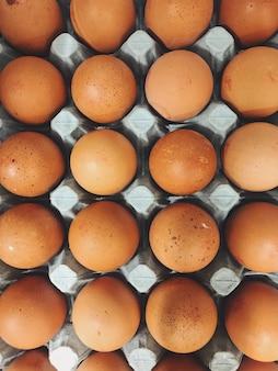 : een verticaal bovenaanzicht van een bakje met bruine eieren