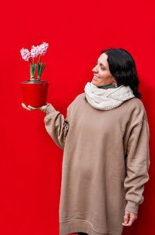Een verticale foto van een mooie vrouw die een pot met hyacintplanten op rode muur houdt