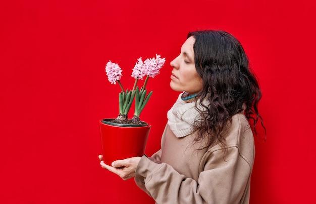 Een verticale foto van een mooie vrouw ruikt een pot met hyacintplanten op een rode muur