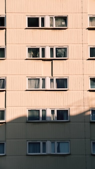 Een verticale opname van een nieuw woongebouw met ramen op een zonnige dag
