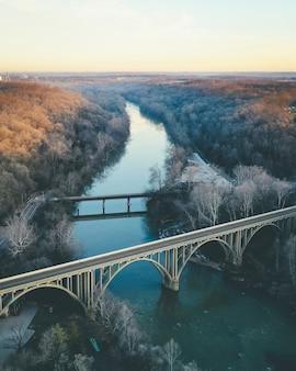 Een verticale opname van een rivier met een stenen brug