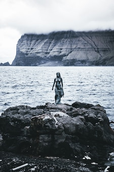 Een verticale opname van een vrouwelijk standbeeld bij de zee
