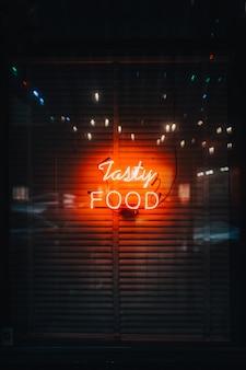 Een verticale opname van felle neonlichten die 'tasty food' spellen