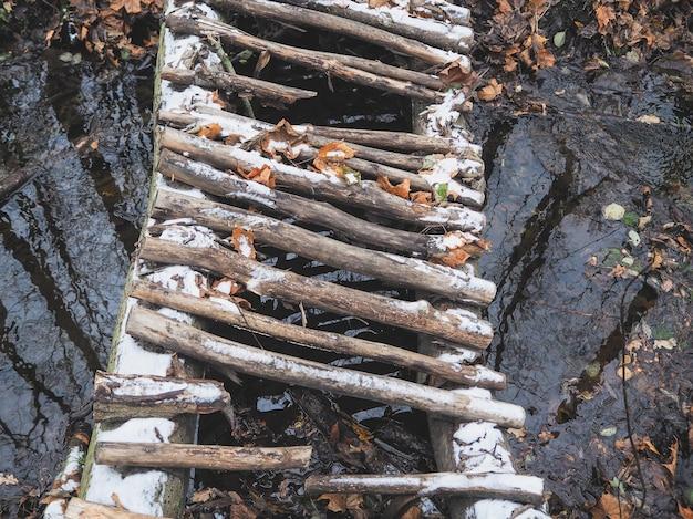 Een vervallen houten brug over de rivier. houten oude brug over een beek op een bospad.