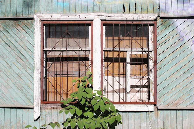 Een vervallen houten verlaten huis. oud gebouw. onbewoond huis. een dichtgetimmerd raam en niemand daar. een gebroken raamclose-up. het rooster op het gebroken raam. vastgoed.