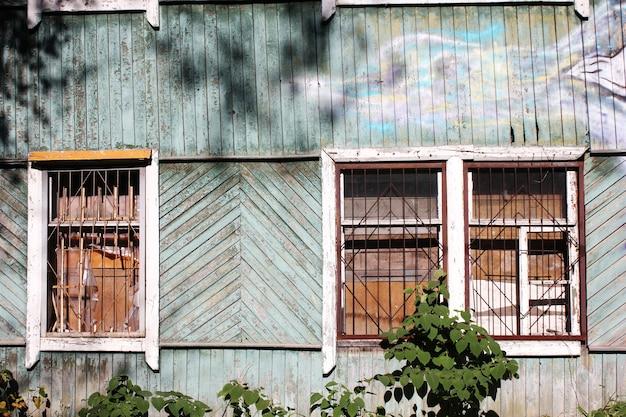 Een vervallen houten verlaten huis. oud gebouw. onbewoond huis. een dichtgetimmerd raam en niemand daar. een gebroken raamclose-up.