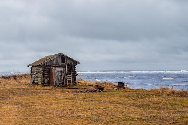 Een vervallen oud vissershuisje in een authentiek dorpje aan de oever van de witte zee. kola-schiereiland. rusland.