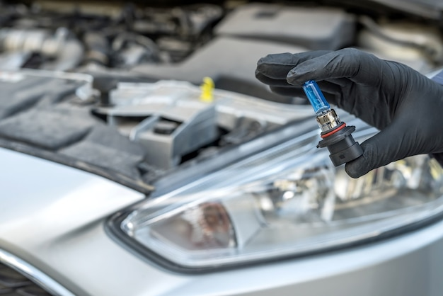 Een vervangende nieuwe, moderne halogeen led-koplamp van de auto installeren. monteur houdt automatische lamp vast