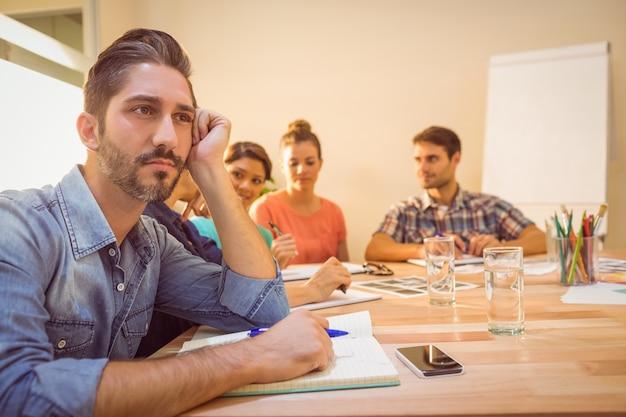Een verveelde ontwerper tijdens een vergadering
