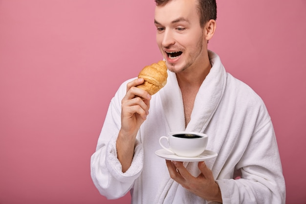 Een verwaande kerel in een witte badjas met croissant