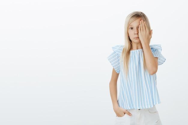 Een verward jong meisje dat zich ongemakkelijk voelt als ze iets schandelijks ziet. schattige schattige dochter met blond haar, één oog bedekt met handpalm