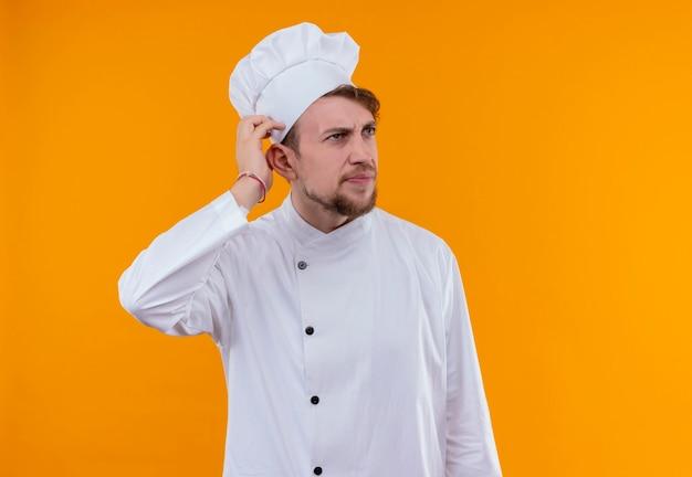 Een verwarde jonge, bebaarde chef-kok in wit uniform houdt zijn hand op zijn hoofd terwijl hij aan een oranje muur denkt