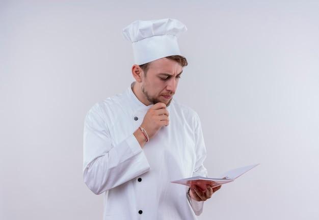 Een verwarde jonge, bebaarde chef-kokmens die een wit fornuisuniform en een hoed draagt en notitieboekje op een witte muur bekijkt