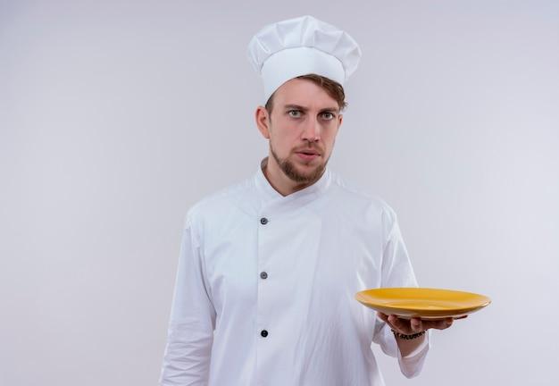 Een verwarde jonge, bebaarde chef-kokmens in wit fornuisuniform en hoed met gele plaat terwijl hij op een witte muur kijkt
