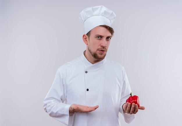 Een verwarde jonge, bebaarde chef-kokmens in wit fornuisuniform en hoed met rode paprika terwijl hij op een witte muur kijkt