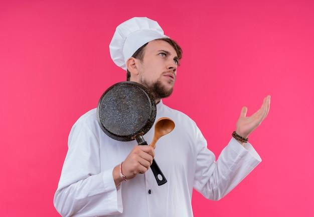 Een verwarde jonge, bebaarde chef-kokmens in wit uniform met koekenpan met houten lepel op een roze muur