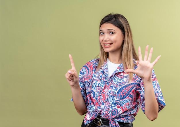 Een verwarde jonge vrouw in een paisley-bedrukt overhemd met nummer zes