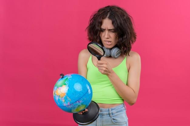 Een verwarde jonge vrouw met kort haar in een groene crop top in koptelefoon kijken wereldbol met vergrootglas