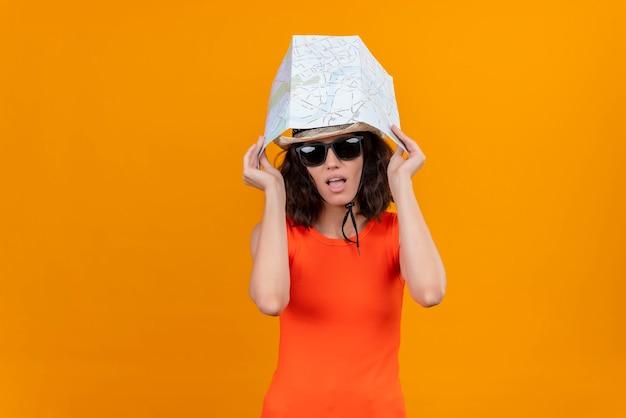 Een verwarde jonge vrouw met kort haar in een oranje overhemd met een zonnehoed en een zonnebril met kaart op het hoofd