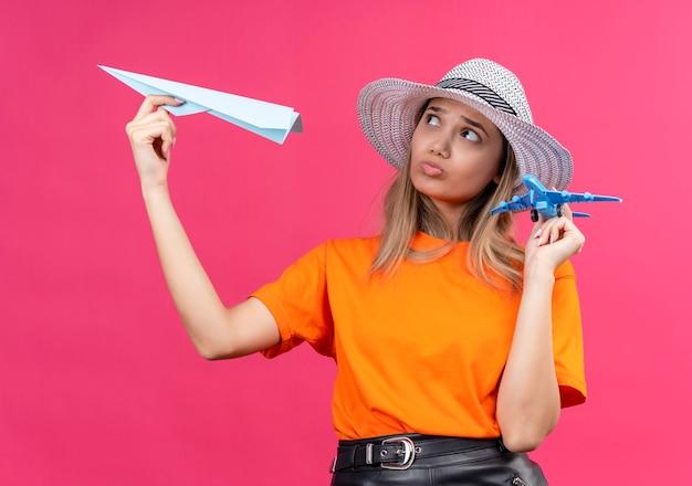 Een verwarde, mooie jonge vrouw in een oranje t-shirt met een zonnehoed op een vliegend papieren vliegtuigje terwijl ze een blauw speelgoedvliegtuig op een roze muur vasthoudt