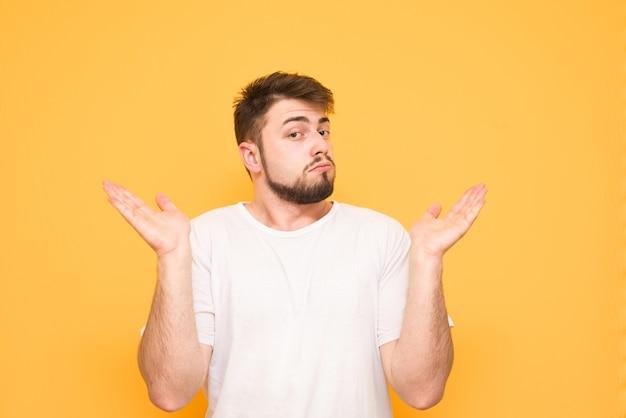 Een verwarde tiener met een baard op geel, die zijn handen heeft opgestoken, weet het antwoord niet