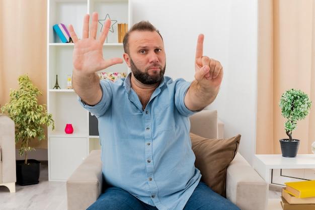 Een verwarde volwassen slavische man zit op een fauteuil en gebaart zes met vingers in de woonkamer