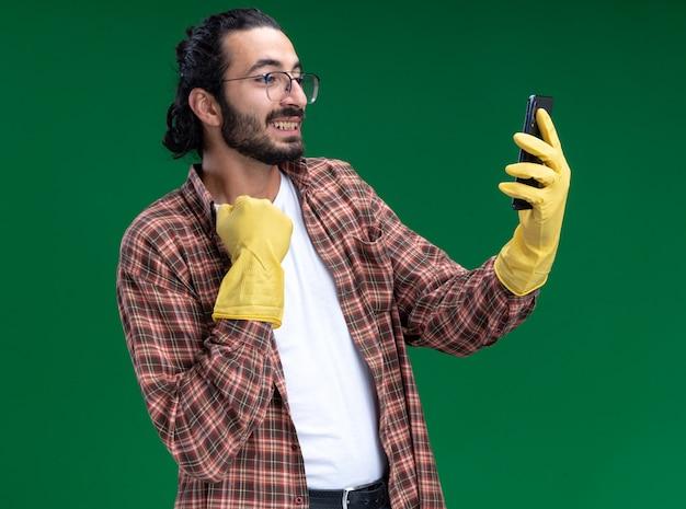 Een verwarmde jonge knappe schoonmaakster met een t-shirt en handschoenen neemt een selfie met een kraag geïsoleerd op een groene muur