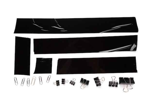Een verzameling gebruikte zwarte elektrische tape-stukken met briefpapierhulpmiddelen