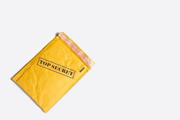Een verzendzak voor brieven of kleine pakjes met tekst top secret op een lichte plek. top geheime informatie. plat, bovenaanzicht