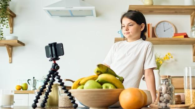 Een videoblogger-meisje neemt videocontent op voor een culinaire blog.
