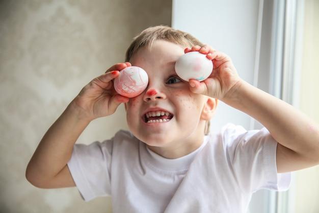 Een vierjarige jongen in een wit t-shirt en een geverfde neus is aan het dommelen om paaseieren in zijn ogen te passen