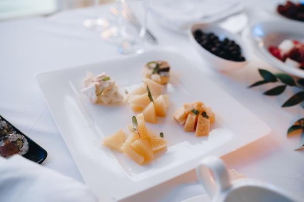Een vierkant bord met verschillende soorten gesneden kaas op een wit tafelkleed