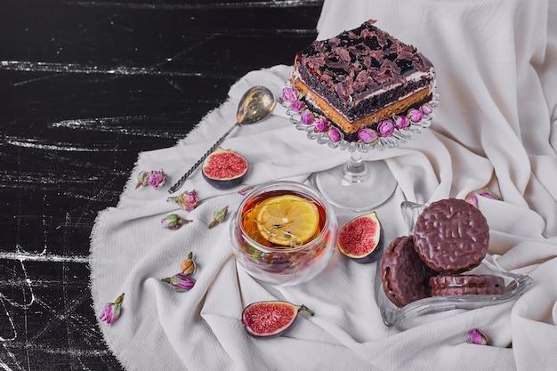 Een vierkant plakje chocolade cheesecake met kruidenthee.