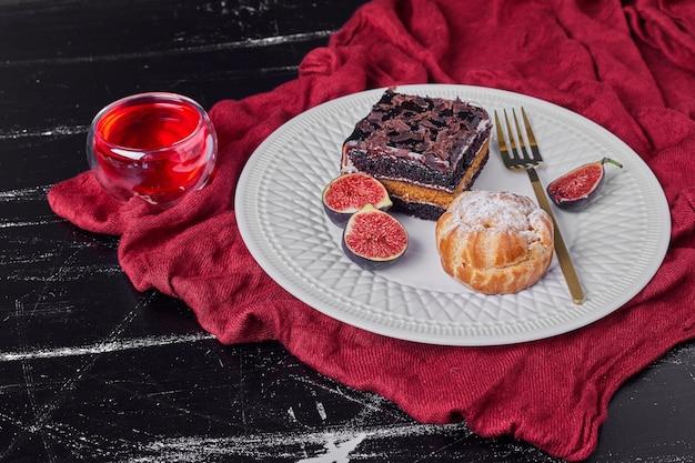 Een vierkant plakje chocolade cheesecake met rode drank
