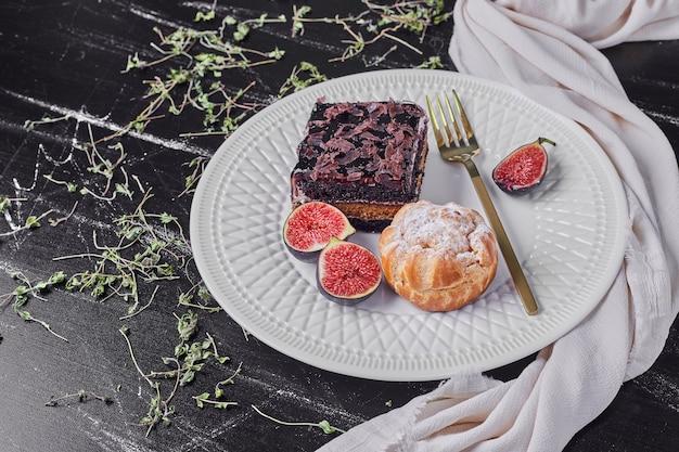 Een vierkant plakje chocolade cheesecake met vijgen en broodje.