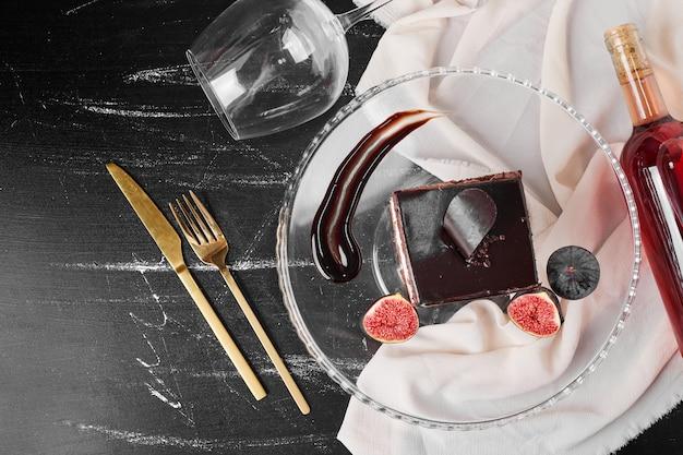 Een vierkant plakje chocolade cheesecake op een glazen schaal.