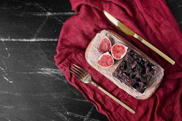 Een vierkant plakje chocolade cheesecake op een houten bord met vijgen.