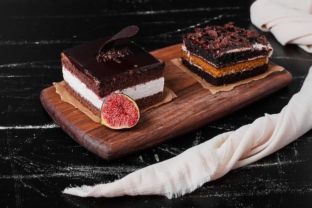 Een vierkant plakje chocolade cheesecake op een houten bord.