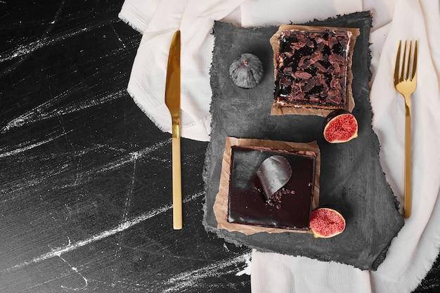 Een vierkant plakje chocolade cheesecake op een stenen bord.
