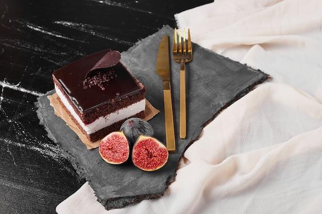 Een vierkant plakje chocolade cheesecake op een stenen schaal.