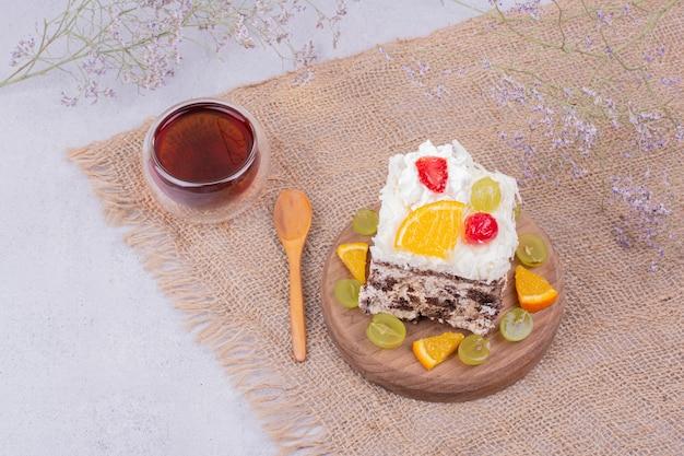 Een vierkant plakje fruitcake met een glas thee.