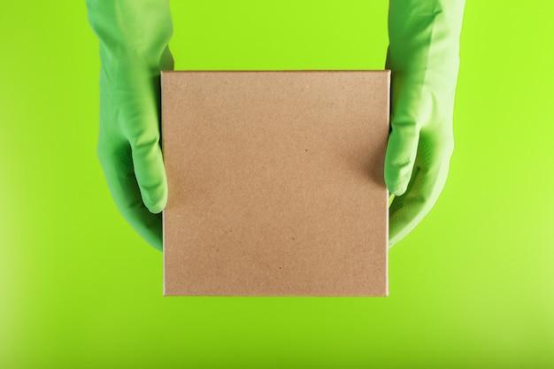 Een vierkante doos in de handen met groene rubberen handschoenen op een groene achtergrond.