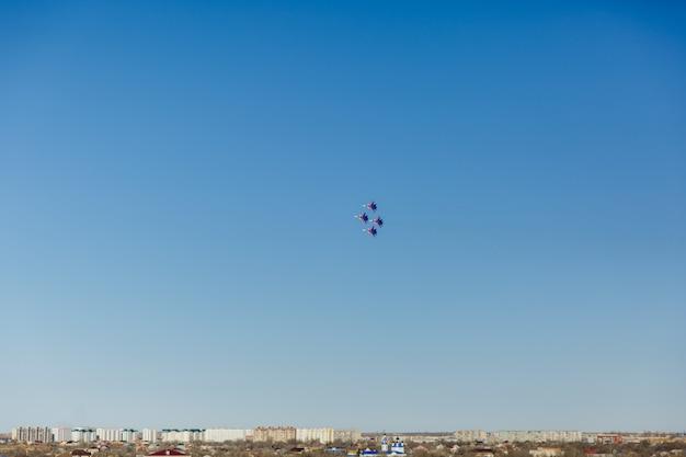 Een vierkante formatie van een groep van vier russische gevechtsvliegtuigen jager vliegen hoog in de blauwe hemel