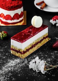 Een vierkante plak aardbeienkaastaart met witte macaron bovenop.
