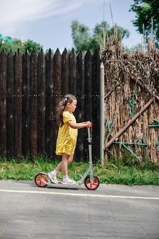Een vijfjarig meisje rijdt op een scooter langs een houten hek in een pretpark tijdens een familieweekend...